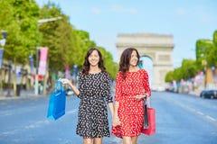 Lyckliga tvilling- systrar som gör shopping på ferier i Frankrike Royaltyfri Fotografi