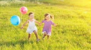 Lyckliga tvilling- systrar som kör runt om att skratta och att spela med ballonger i sommar Arkivfoton