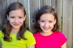 Lyckliga tvilling- systrar som ler på den wood trädgården, fäktar royaltyfria foton