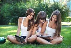 Lyckliga ung flicka studerar i en park Arkivfoto