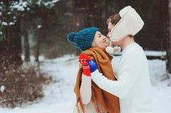 lyckliga unga älska par som går i den snöig vinterskogen som täckas med snö royaltyfria foton