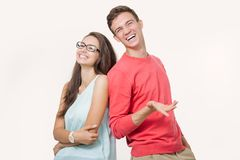 Lyckliga unga älskvärda par som tillbaka står till baksida och ler se kameran på vit bakgrund fotografering för bildbyråer