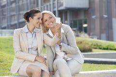Lyckliga unga affärskvinnor som tar självståenden till och med mobiltelefonen mot kontorsbyggnad Royaltyfria Bilder