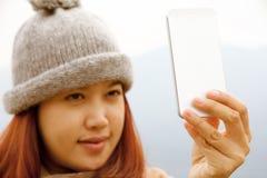 Lyckliga unga asiatiska kvinnor ser hennes mobiltelefon Royaltyfria Foton
