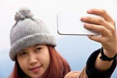 Lyckliga unga asiatiska kvinnor ser hennes mobiltelefon Royaltyfri Bild