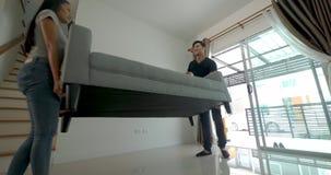 Lyckliga unga asiatiska par som flyttar en soffa under deras flyttning in i nytt hus lager videofilmer