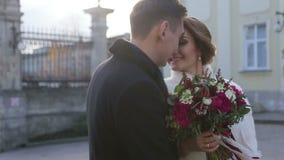 Lyckliga unga attraktiva brölloppar som omfamnar och ler slappt nära kyrkan Kamerarörelse i ultrarapid arkivfilmer