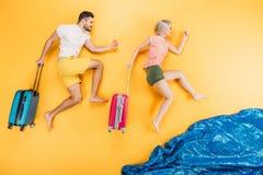 lyckliga unga barfota par med resväskor som kör på guling, sommar fotografering för bildbyråer