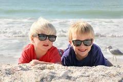 Lyckliga unga barn som lägger i solen på stranden Arkivbilder