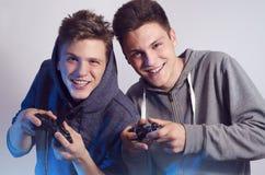 Lyckliga unga bröder som spelar videospel, selektiv fokus på framsidor arkivfoton