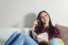 Lyckliga unga brunettkvinnadrömmar av en resasemester som ligger på en vit soffa med en dagbok Royaltyfria Bilder