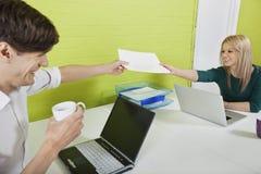 Lyckliga unga businesspeople som till varandra passerar dokument med bärbara datorer på skrivbordet Fotografering för Bildbyråer