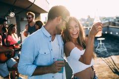 Lyckliga unga dansa par som har gyckel och tycker om partiet på sommar arkivfoton