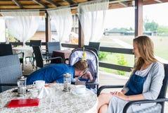 Lyckliga unga föräldrar dricker te med behandla som ett barn sonen Fotografering för Bildbyråer