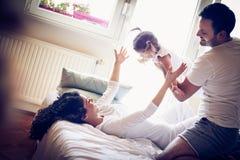 Lyckliga unga föräldrar med deras liten flicka har att spela royaltyfri fotografi