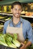 Lyckliga unga försäljningar är kontorist hållande bok som är choy i supermarket royaltyfri bild
