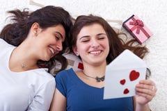 Lyckliga unga flickor som läser förälskelsebrevet Arkivbild