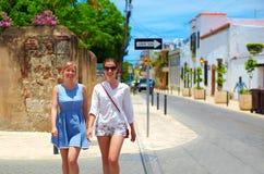 Lyckliga unga flickor, turister som går på gator i stad, turnerar, Santo Domingo Arkivbild