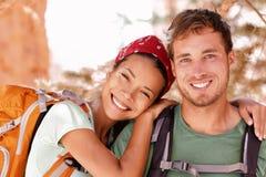 Lyckliga unga fotvandrare som vandrar på sommarlopp arkivfoto