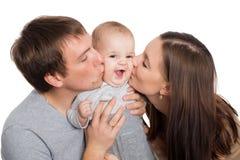 Lyckliga unga föräldrar kysser en älskad son Fotografering för Bildbyråer