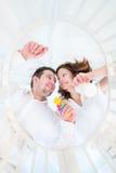 Lyckliga unga föräldrar som står på säng av deras, behandla som ett barn behandla som ett barn Royaltyfri Foto