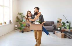 Lyckliga unga gift parflyttningar till den nya lägenheten royaltyfri bild