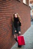 Lyckliga unga härliga kvinnor som rymmer shoppingpåsar som går i väg från, shoppar på stadsgatan Sale, consumerism och folk arkivbild