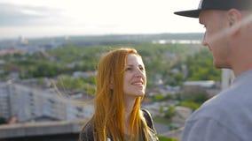 Lyckliga unga härliga stilfulla par som ger affektion till varje vän på taket av huset lager videofilmer