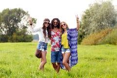 Lyckliga unga hippievänner som utomhus visar fred Arkivfoto