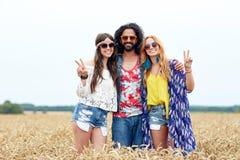 Lyckliga unga hippievänner som utomhus visar fred Arkivbilder
