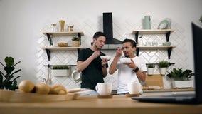 Lyckliga unga homosexuella par, glat folk, manlig partner som hemma äter frukosten i kök arkivfilmer