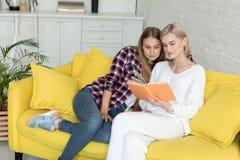 Lyckliga unga kvinnliga lesbiska par i tillf?llig kl?der som tillsammans hemma sitter p? den gula soffan, l?ser den nya boken arkivbild