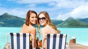 Lyckliga unga kvinnor i bikini med drinkar på stranden royaltyfria foton