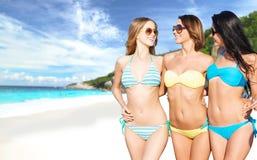 Lyckliga unga kvinnor i bikinier på sommar sätter på land Royaltyfria Bilder