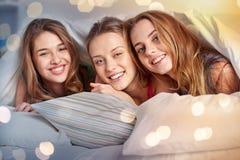 Lyckliga unga kvinnor i hemmastatt pajamaparti för säng arkivfoton