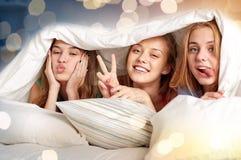 Lyckliga unga kvinnor i hemmastatt pajamaparti för säng royaltyfria foton