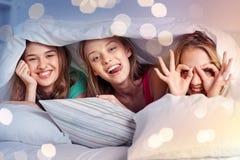 Lyckliga unga kvinnor i hemmastatt pajamaparti för säng royaltyfria bilder