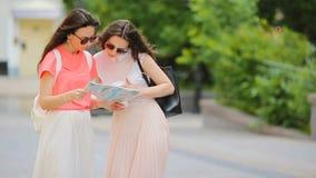 Lyckliga unga kvinnor med översikten som promenerar stadsgatan i Europa