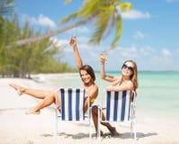 Lyckliga unga kvinnor med drinkar som solbadar på stranden Arkivfoton
