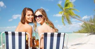 Lyckliga unga kvinnor med drinkar som solbadar på stranden Royaltyfri Bild