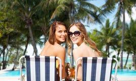 Lyckliga unga kvinnor med drinkar som solbadar på stranden Fotografering för Bildbyråer