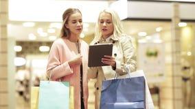 Lyckliga unga kvinnor med minnestavlaPC och shoppingpåsar arkivfilmer