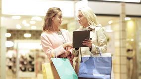 Lyckliga unga kvinnor med minnestavlaPC och shoppingpåsar stock video