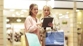 Lyckliga unga kvinnor med minnestavlaPC och shoppingpåsar lager videofilmer