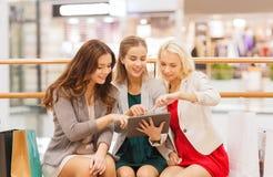 Lyckliga unga kvinnor med minnestavlaPC och shoppingpåsar Fotografering för Bildbyråer