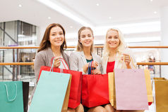 Lyckliga unga kvinnor med shoppingpåsar i galleria Royaltyfri Bild
