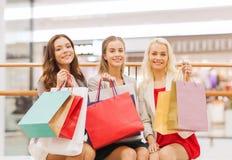 Lyckliga unga kvinnor med shoppingpåsar i galleria Royaltyfri Fotografi