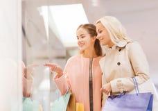 Lyckliga unga kvinnor med shoppingpåsar i galleria Arkivbilder