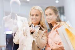 Lyckliga unga kvinnor med shoppingpåsar i galleria Royaltyfria Bilder