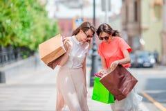 Lyckliga unga kvinnor med shoppingpåsar tycker om deras köp som promenerar stadsgatan Sale, consumerism och folk Fotografering för Bildbyråer